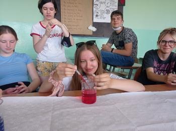 uczennica klasy 8A nalewa kropelki zabarwionej wody do probówki wypełnionej olejem