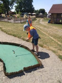 dzieci grają w mini golfa