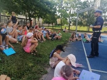 Grupa dzieci słucha policjanta