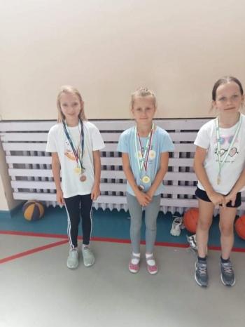 Dziewczynki w sali gimnastycznej z medalami.jpeg